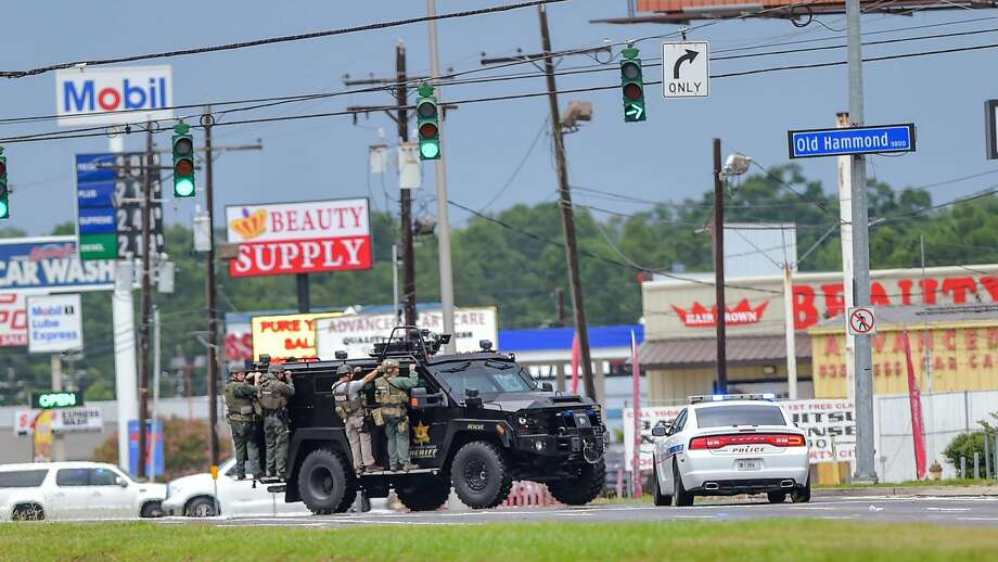 Baton Rouge Police search for a shooting suspect near Hammond Aire Shopping Center after multiple police were shot on Sunday, July, 17, 2016. Multiple law enforcement officers were killed and wounded Sunday morning in a shooting near a gas station in Baton Rouge, less than two weeks after a black man was shot and killed by police here, sparking nightly protests across the city. Photo: Scott Clause, Associated Press