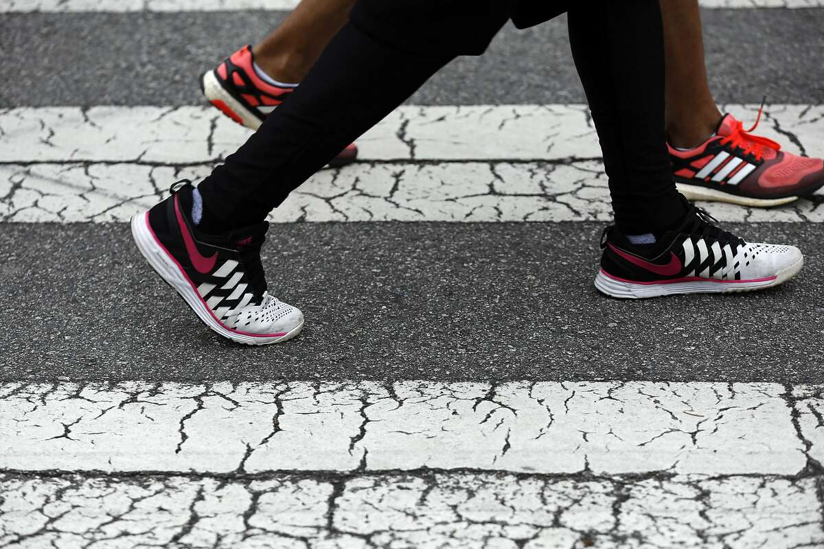 A pair of participants stride down the street during the 30th annual AIDS Walk San Francisco at Golden Gate Park in San Francisco, California, on Sunday, July 17, 2016.