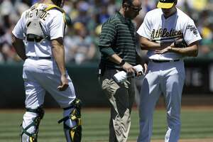 Oakland Athletics pitcher Rich Hill, right, has his hand examined by a trainer in the first inning of a baseball game against the Toronto Blue Jays as Athletics catcher Matt McBride, left, watches on Sunday, July 17, 2016, in Oakland, Calif. Hill left the game in the first inning. (AP Photo/Ben Margot)