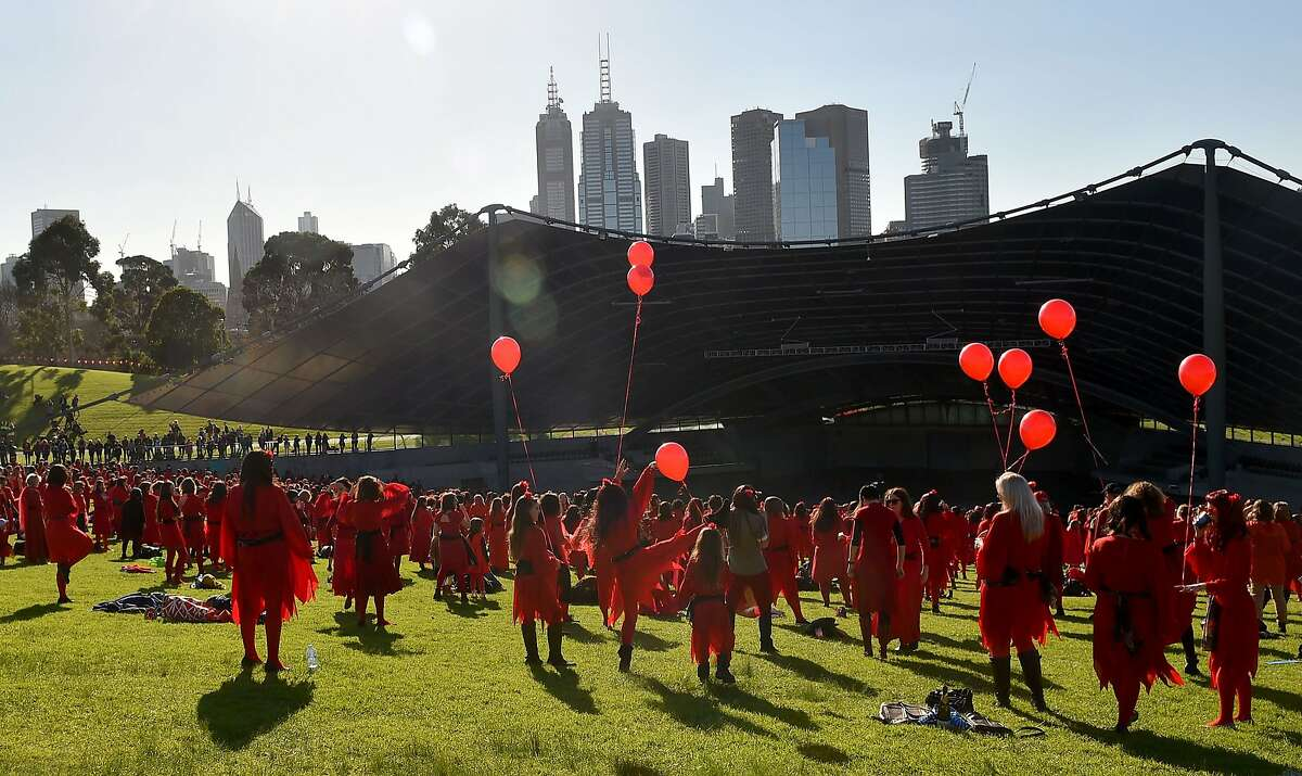 Kate Bush fans gather to rehearse a dance before performing during a celebration to mark 'The Most Wuthering Heights Day Ever' in Melbourne on July 16, 2016. Thousands of Kate Bush fans put on their best billowy red dresses and danced en masse in Melbourne on July 14 to one of the singer's most iconic songs Wuthering Heights. / AFP PHOTO / Paul CrockPAUL CROCK/AFP/Getty Images