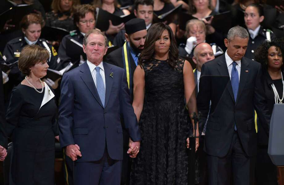 "TOPSHOT - L-R: Former first lady Laura Bush, former US president George W. Bush, US First Lady Michelle Obama and US President Barack Obama join hands during the singing of ""The Battle Hymn of the Republic"" during an interfaith memorial service for the victims of the Dallas police shooting at the Morton H. Meyerson Symphony Center on July 12, 2016 in Dallas, Texas. President Barack Obama attended a somber memorial Tuesday to five police officers slain in a sniper ambush in Dallas, as he seeks to unify a country divided by race and politics. / AFP PHOTO / MANDEL NGANMANDEL NGAN/AFP/Getty Images Photo: MANDEL NGAN, Staff / AFP/Getty Images / AFP or licensors"