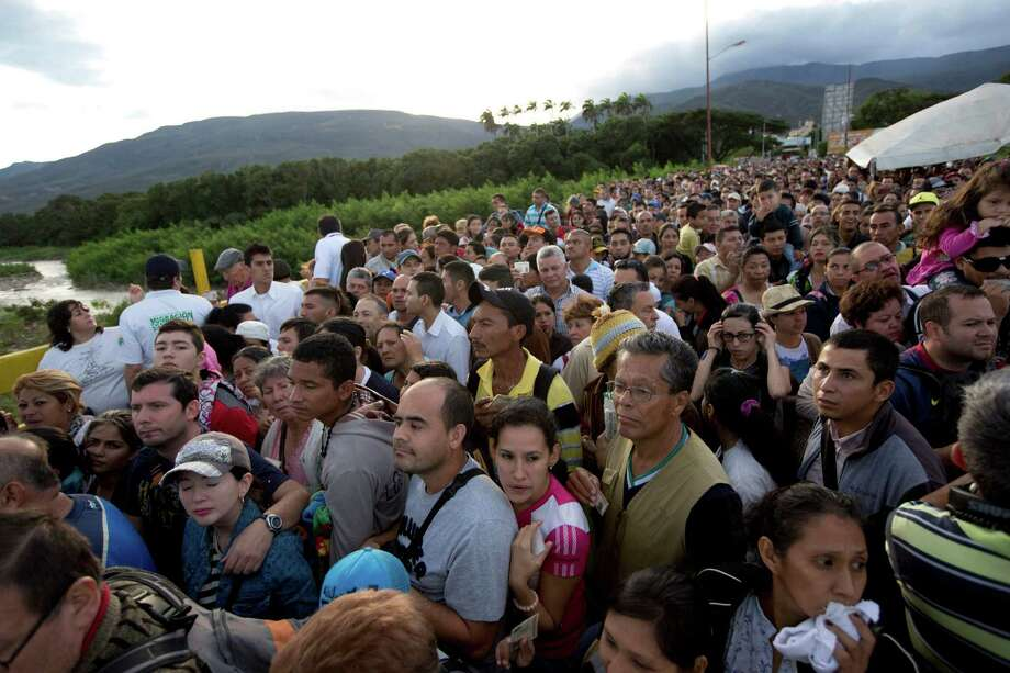 Venezuelans cross the Simon Bolivar bridge linking San Antonio del Tachira, Venezuela, with Cucuta, Colombia, to buy supplies, Sunday, July 17, 2016. Tens of thousands of Venezuelans crossed the border into Colombia on Sunday to hunt for food and medicine that are in short supply at home. It's the second weekend in a row that Venezuela's government has opened the long-closed border connecting Venezuela to Colombia, and by 6 a.m., a line of would-be shoppers snaked through the entire town of San Antonio del Tachira. (AP Photo/Ariana Cubillos) Photo: Ariana Cubillos, STF / Copyright 2016 The Associated Press. All rights reserved. This material may not be published, broadcast, rewritten or redistribu