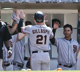 San Francisco Giants' Conor Gillaspie high-fives teammates after hitting a three-run home run against the San Diego Padres in the seventh inning of a baseball game Sunday, July 17, 2016, in San Diego. (AP Photo/Lenny Ignelzi)