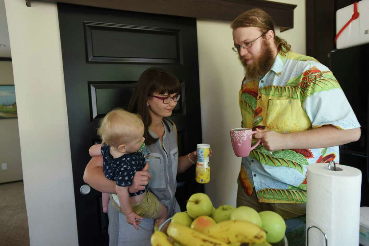 Damian Nowak, wife Hanna and son Bill converse in their Floresville home. He pays almost $700 a month for a Blue Cross Blue Shield of Texas plan that covers him and his family. The insurer proposes raising that to $1,069 a month.
