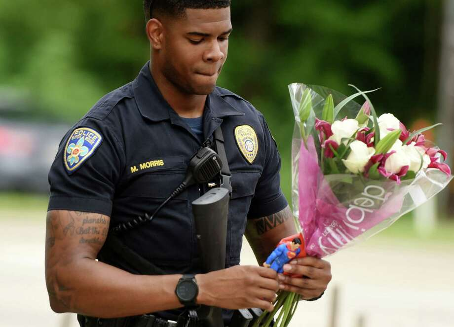 Baton Rouge Police Department Officer Markell Morris holds a bouquet of flowers and a Superman action figure that a citizen left at the Our Lady of the Lake Hospital where the police officers were brought this morning, Sunday, July 17, 2016. Multiple law enforcement officers were killed and wounded Sunday morning in a shooting near a gas station in Baton Rouge. (Henrietta Wildsmith/The Times via AP) Photo: Henrietta Wildsmith, Associated Press / The Times
