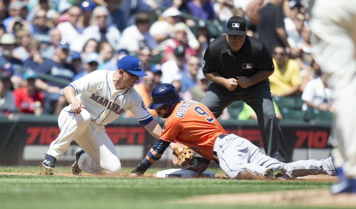 SEATTLE, WA - JULY 17: Third baseman Kyle Seager #15, left, of the Seattle Mariners is unable to hold on to a throw by catcher Jesus Sucre #2 of the Seattle Mariners as a stealing Marwin Gonzalez #9 of the Houston Astros slides into third base during the first inning at Safeco Field on July 17, 2015 in Seattle, Washington. Gonzalez would score on the fielding error. (Photo by Stephen Brashear/Getty Images) Mariners vs. Astors