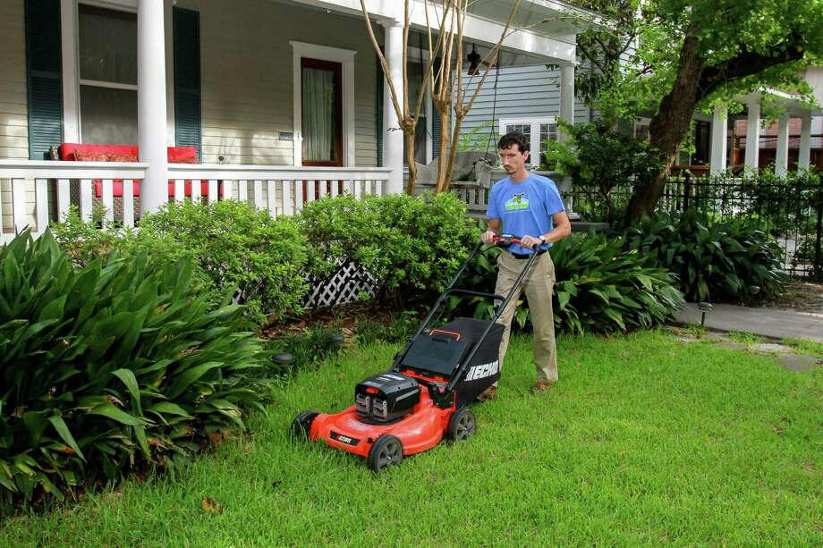 Clean Air Lawn Care technician Andrey Morozov mows a customer's yard. The mower's engine gets its power from solar panels.  Photo: Gary Fountain, For The Chronicle / Copyright 2016 Gary Fountain