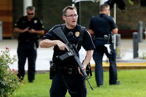 Police guard the emergency room entrance of Our Lady Of The Lake Medical Center, where wounded officers were brought Sunday, in Baton Rouge, La., after a shootout that killed three other officers.
