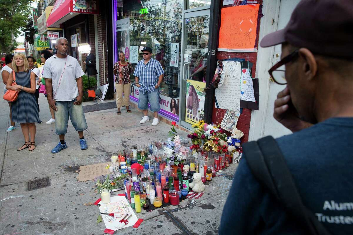 FILE - In this July 22, 2014 file photo, pedestrians stand beside a memorial for Eric Garner at the site where he died while being arrested by New York City police, in the Staten Island borough of New York. Two years after the police chokehold death of Garner made