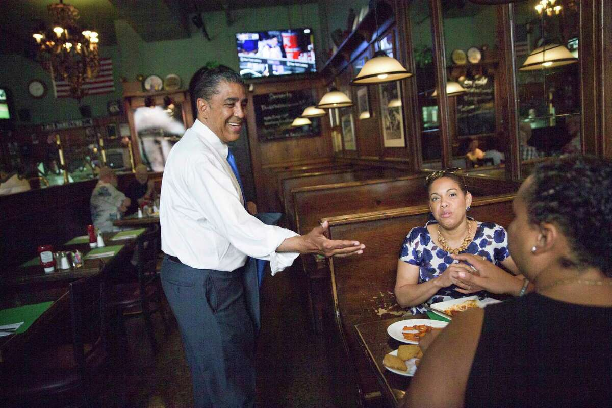 In this Wednesday, July 6, 2016 photo, Adriano Espaillat, left, greets diners at a restaurant in the Inwood neighborhood of Manhattan. In an election year filled with debate over immigration, Espaillat hopes his personal story makes its own statement. After living at one point in the country without documentation, he could become the first Dominican-American in Congress. (AP Photo/Mary Altaffer) ORG XMIT: NYMA301