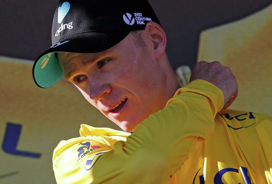 Chris Froome adjusts the yellow jersey, something he has possessed for the eighth consecutive day after Sunday's stage. Photo: Christophe Ena, STF / AP