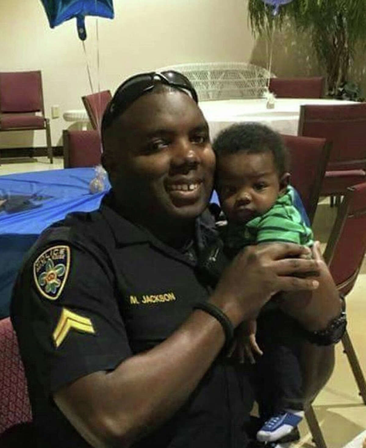 In this 2016 photo provided by Trenisha Jackson, her husband, Baton Rouge Police Officer Montrell Jackson, holds his son Mason at a Father's Day event for police officers in Baton Rouge, La. Montrell Jackson and two other Baton Rouge law enforcement officers investigating a report of a man with an assault rifle were killed Sunday, less than two weeks after a black man was fatally shot by police here in a confrontation that sparked nightly protests that reverberated nationwide. (Courtesy of Trenisha Jackson via AP) ORG XMIT: NY112