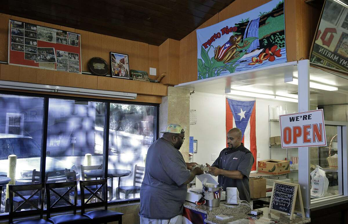 Eric Rivera helps Champ Green at the Puerto Rican restaurant, Borinquen, he co-owns with Christopher Caraballo in the Fruitvale district of Oakland, Calif., on Thursday, July 14, 2016. Christopher Caraballo and Eric Rivera run a permanent pop-up in a convenience store that specializes in Puerto Rican food. They learned to cook these recipes by filming Christopher's mother on his iPhone, and specialize in arroz con gandules (rice with pigeon peas).