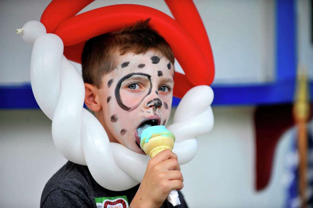Eliot Merritt, 7, from East Greenbush, with his face painted to look like a puppy, eats his ice cream at MoxieOs ice cream stand on National Ice Cream Day, Sunday, July 17, 2016, in Wynantskill, N.Y. Moxie's has been holding a huge celebration on National Ice Cream Day for over 10 years. Pamela Allie-Morrill, who took over the stand from her parents in 2001, said that along with celebrating ice cream day it's also a day to show our appreciation for our wonderful customers. Moxie's opens on Mother's Day each year, with 25 to 30 flavors and peaks around National Ice Cream Day, 70 flavors this season. Moxie's closes when they run out of their flavors, usually sometime in the last week of August. The signature flavor of the stand is blue moon,