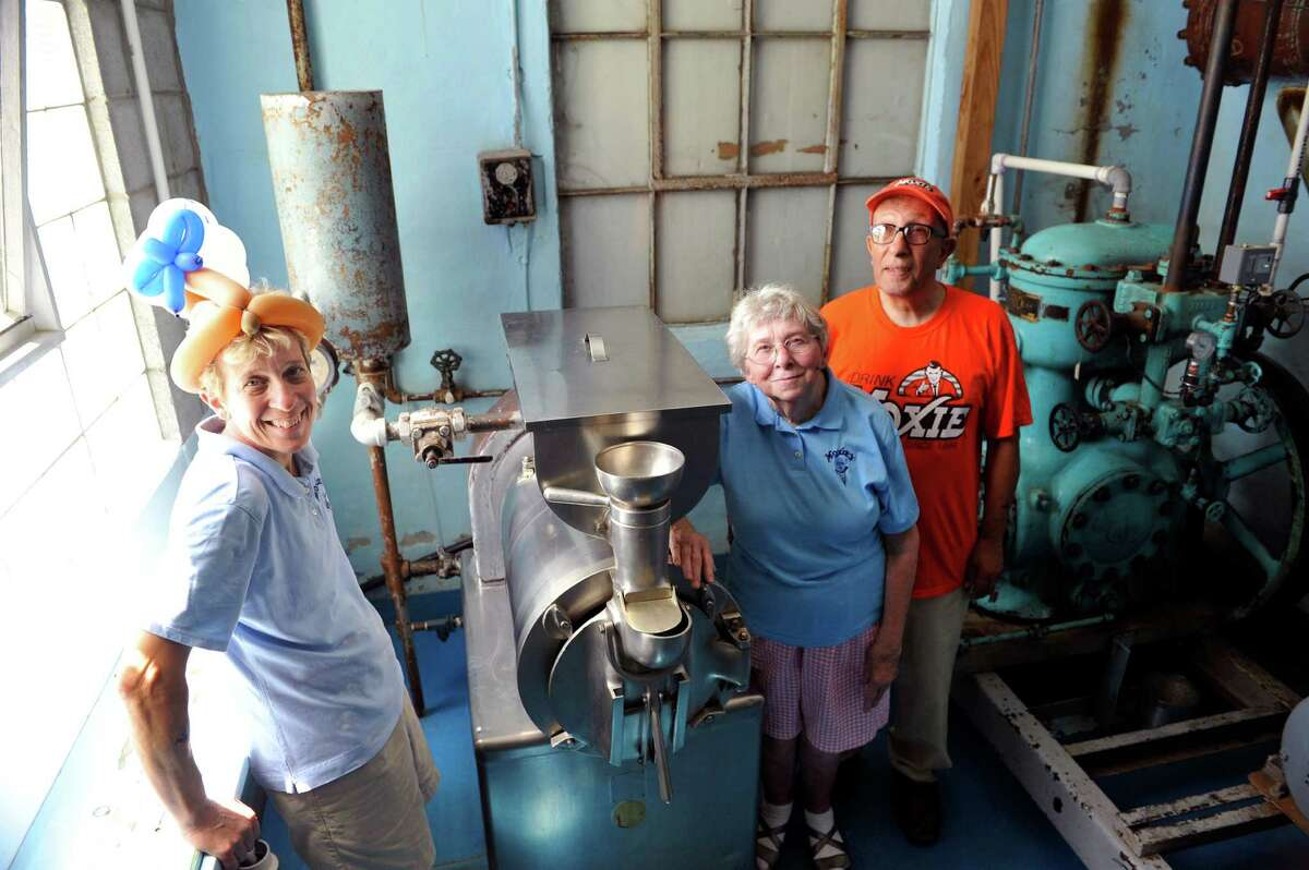 Pamela Allie-Morrill, left, owner of MoxieOs ice cream stand, poses with her parents, Geraldine and Mohamed Allie, next to the one ice cream making machine they use at MoxieOs on National Ice Cream Day, Sunday, July 17, 2016, in Wynantskill, N.Y. Moxie's has been holding a huge celebration on National Ice Cream Day for over 10 years. Pamela Allie-Morrill, who took over the stand from her parents in 2001, said that along with celebrating ice cream day it's also a day to show our appreciation for our wonderful customers. Moxie's opens on Mother's Day each year, with 25 to 30 flavors and peaks around National Ice Cream Day, 70 flavors this season. Moxie's closes when they run out of their flavors, usually sometime in the last week of August. The signature flavor of the stand is blue moon,