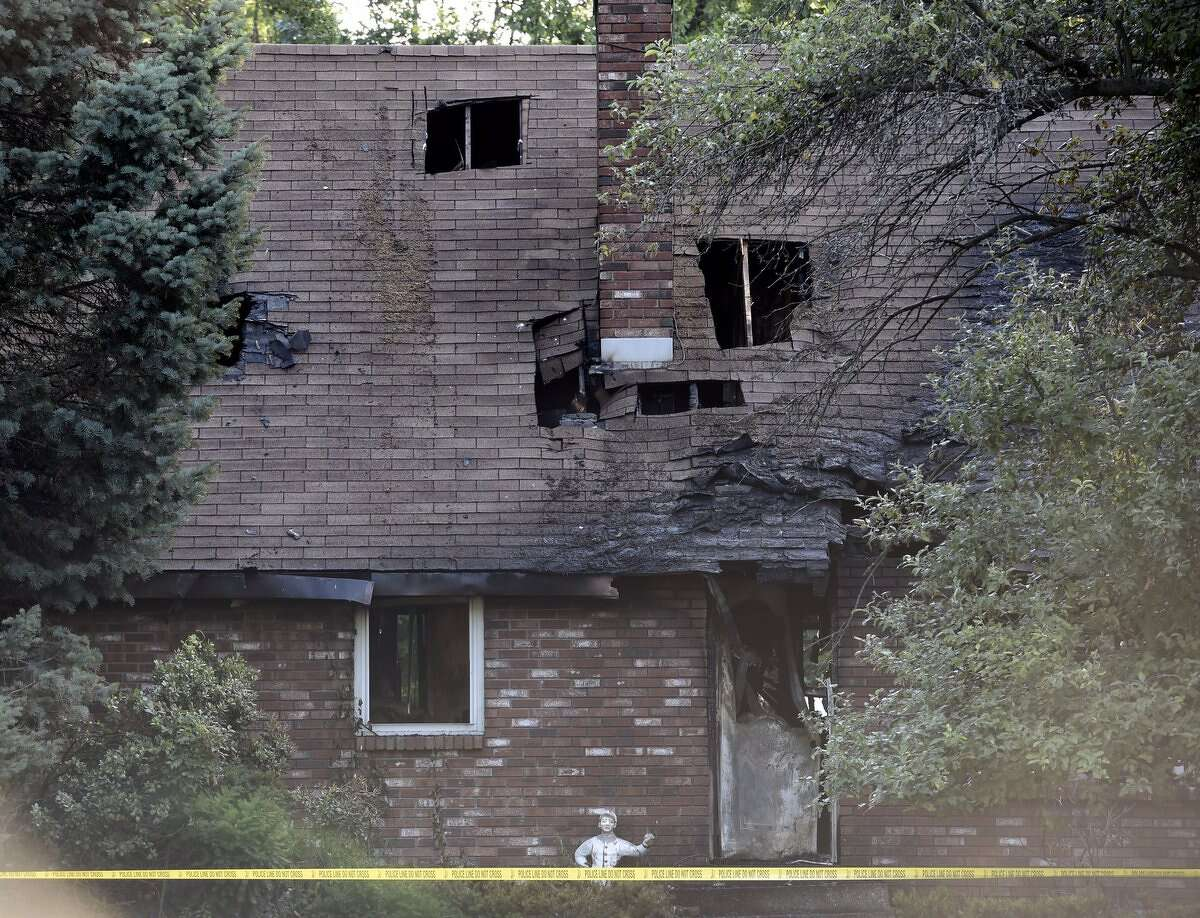 A lone police officer stands guard Monday morning at the scene of a house fire Sunday on Carman Road in Guilderland that left one person dead. (Skip Dickstein / Times Union)