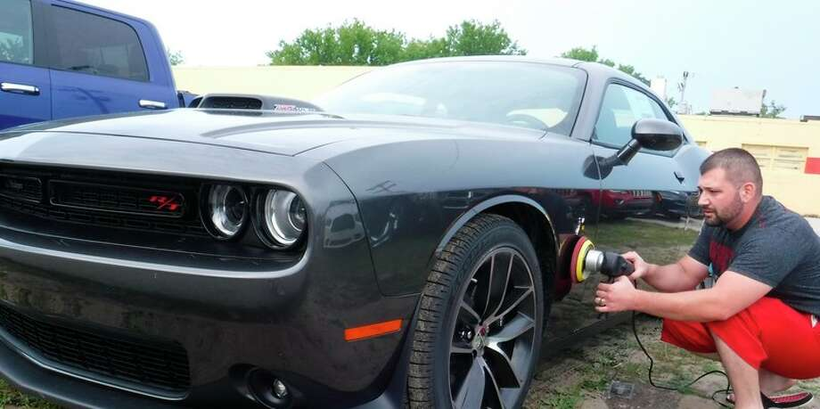 Ryan Wakefield, owner of On-Site Auto Detailing, buffs and adds permanent paint protection to a Challenger Hellcat.