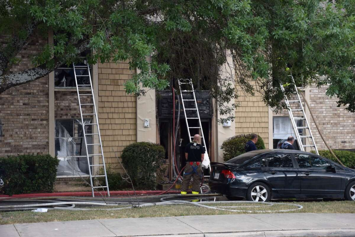 San Antonio Fire Department crews work the scene of an apartment complex fire on the North Side in the 9500 block of Lorene Lane after three young children jumped out of a window into the arms of a SAPD officer.