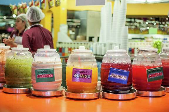 Assorted flavors of Aguas frescas sit on the counter at the juice bar at Mi Tienda Wednesday July 13, 2016. (Michael Starghill, Jr.)