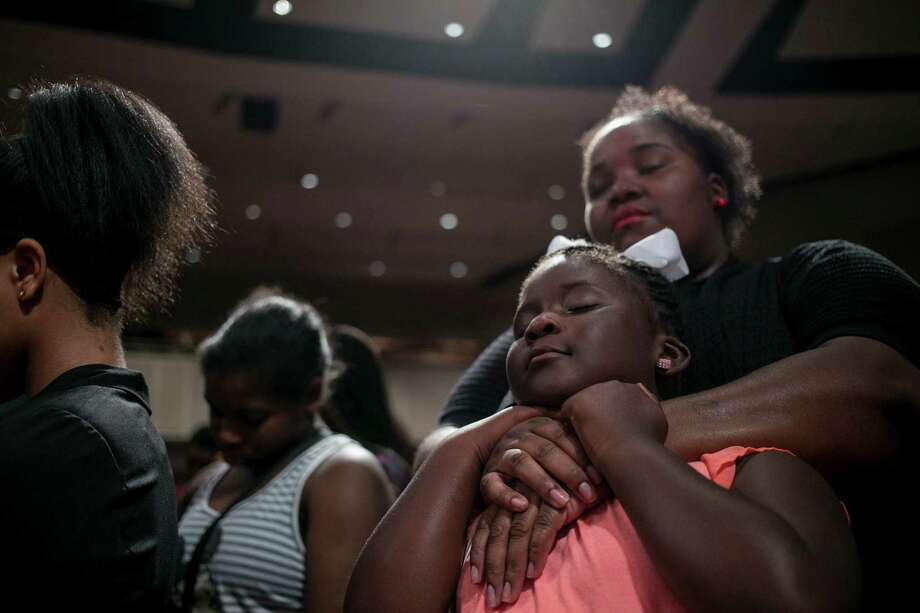 People pray at Friendship-West Baptist Church in Dallas during a service focused on the two black men killed by police in Minnesota and Louisiana, as well as the five police officers killed in the north Texas city. Photo: ILANA PANICH-LINSMAN, STR / NYTNS