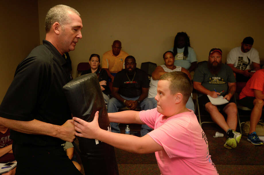 Kevan Robinson teaches James Graham, 13, a blocking technique during a class for youth football coaches in Kountze on Saturday. The USA Football class was to teach coaches safer techniques for players to block and tackle.  Photo taken Saturday 7/16/16 Ryan Pelham/The Enterprise Photo: Ryan Pelham / ©2016 The Beaumont Enterprise/Ryan Pelham