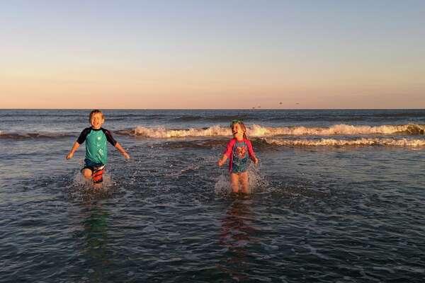 Pete Tedesco, 6, and Sophie Tedesco, 5, splash at the beach on Galveston Island.