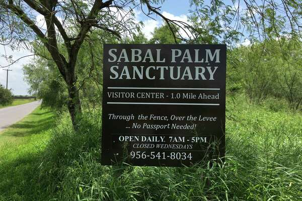 A sign at the entrance of Sabal Palms Sanctuary, with a bit of tongue-in-cheek reference to the border fence, and visitors not required to bring a passport to enter.