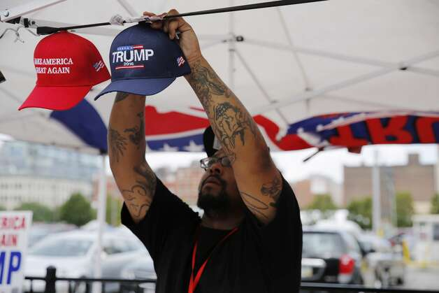 """A vendor displays souvenir hats on the first day of the Republican National Convention on July 18, 2016, in Cleveland, Ohio. Trump or Biden apparel — Prohibited No matter how good you may look in your Trump or Biden T-shirt, state law mandates you leave it tucked away in a drawer back home on Election Day. Connecticut law states that voters are not allowed to do any """"electioneering"""" in the polling place, and this rule extends to clothing. In translation, voters cannot wear anything that has a candidate's name or likeness printed on it. The rule applies to all candidates, not just presidential candidates. So anything with a large """"HAYES 2020"""" printed on it or a picture of David Sullivan, is off limits. If a person does show up to the polls with such a T-shirt, it will have to be turned inside out or covered while voting. Photo: DOMINICK REUTER/AFP/Getty Images"""