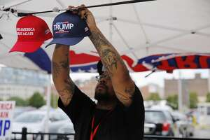 A vendor displays souvenir hats on the first day of the Republican National Convention on July 18, 2016, in Cleveland, Ohio. Thousands of delegates descended on a tightly secured Cleveland arena Monday for the opening of the Republican National Convention, with Donald Trump's wife playing character witness as the tough-talking mogul locks up his party's presidential nomination. / AFP / DOMINICK REUTER        (Photo credit should read DOMINICK REUTER/AFP/Getty Images)