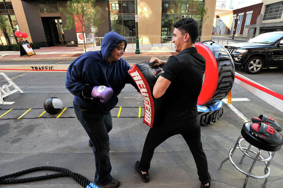 Ilyssa Gormley, left, competes in a challenge to win a free four-day pass to the UFC Gym with the help of UFC Gym's assistant general manager Damien Nikolao in front of the gym on Summer Street during Park(ing) Day in downtown Stamford, Conn., on Friday, Sept. 18, 2015. Park(ing) Day started in 2005 in San Francisco and grew into a worldwide event where cities opened up public parking spots to local businesses to offer free services in an experiment to activate public spaces. Photo: Jason Rearick / Hearst Connecticut Media / Stamford Advocate