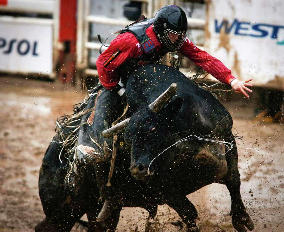 Cody Teel, from Kountze, Texas, stays on Bottle Rocket to win the bull riding event during the rodeo finals at the Calgary Stampede in Calgary, Alberta, Sunday, July 17, 2016. (Jeff McIntosh/The Canadian Press via AP) Photo: Jeff McIntosh, SUB / The Canadian Press