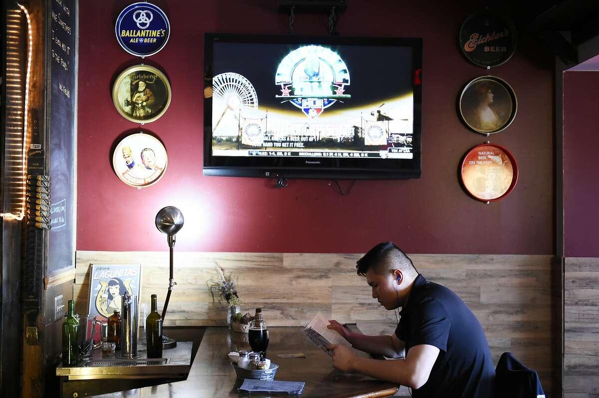 Cedric Tsui of San Francisco, reads at the bar on Saturday, July 16, 2016 at Dark Horse Inn in San Francisco, California.