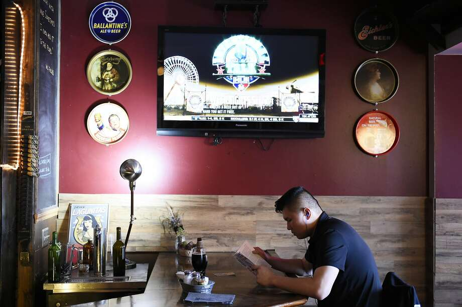 Cedric Tsui reads at the bar at the Dark Horse Inn in S.F.'s Excelsior neighborhood, which data reveal has the slowest-growing restaurant strip in S.F. Photo: Michael Noble Jr., The Chronicle