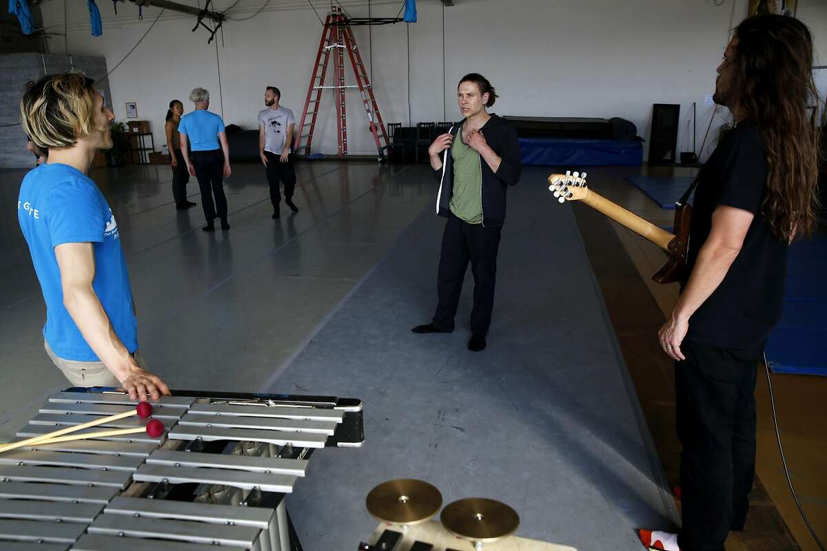 Robert Dekkers (center) discusses the tempo of the music with Andy Meyerson (left) and Travis Andrews during a rehearsal of