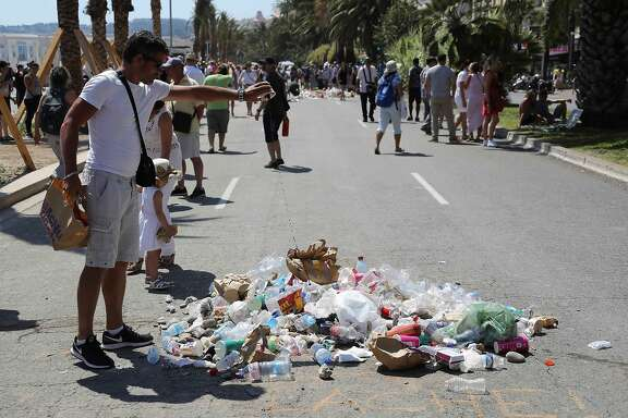"""People throw garbage on July 18, 2016 on the Promenade des Anglais seafront in Nice, at the site where Mohamed Lahouaiej-Bouhlel, a 31-year-old Tunisian who drove a truck into a crowd watching a fireworks display on Bastille Day, was killed by the police. The message reads """"coward"""". France was set to hold a minute's silence on July 18, 2016 to honour the 84 victims of the Nice truck attack, but a period of national mourning was overshadowed by bickering politicians. Church bells will toll across the country, and the country will fall silent at midday, a now grimly familiar ritual after the third major terror attack in 18 months on French soil. / AFP PHOTO / Valery HACHEVALERY HACHE/AFP/Getty Images"""