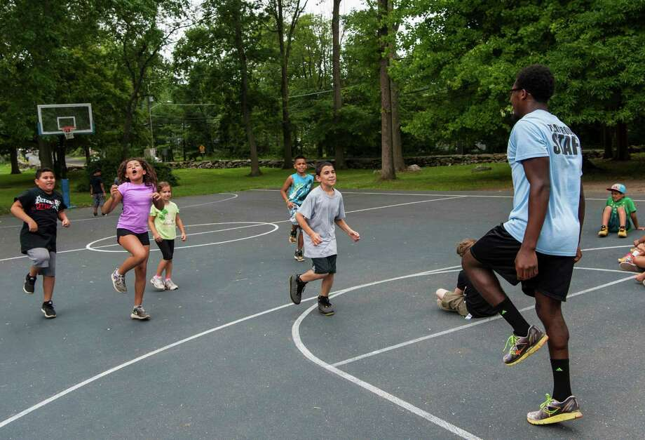 Camp Counselor Jamal Barrett leads a game of Simon Sez at the Belltown Camp held at Barrett Park, Stamford, CT Thursday, July 14, 2016. Photo: Mark Conrad / For Hearst Connecticut Media / ©Mark F Conrad