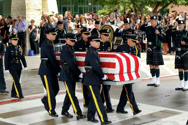 The Dallas Police Honor Guard carries the flag-draped casket of Dallas police officer Michael Krol to a ceremony outside of Prestonwood Baptist Church in Plano on July 15. Krol was gunned down in an ambush attack in downtown Dallas on July 7.