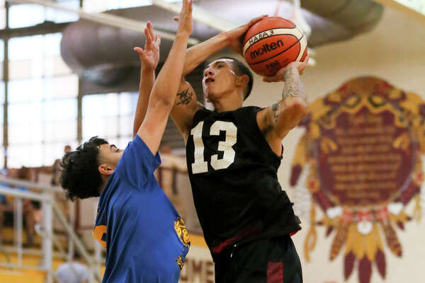 Joel Gonzales (right) playing with the '07 Elites, tries to shoot over the Splash Bros' Jake Martinez during warm up games in the men's bracket of the 11th Annual Harlandale Alumni Basketball Association Tournament at Harlandale High School on Friday, July 15, 2016.  MARVIN PFEIFFER/ mpfeiffer@express-news.net