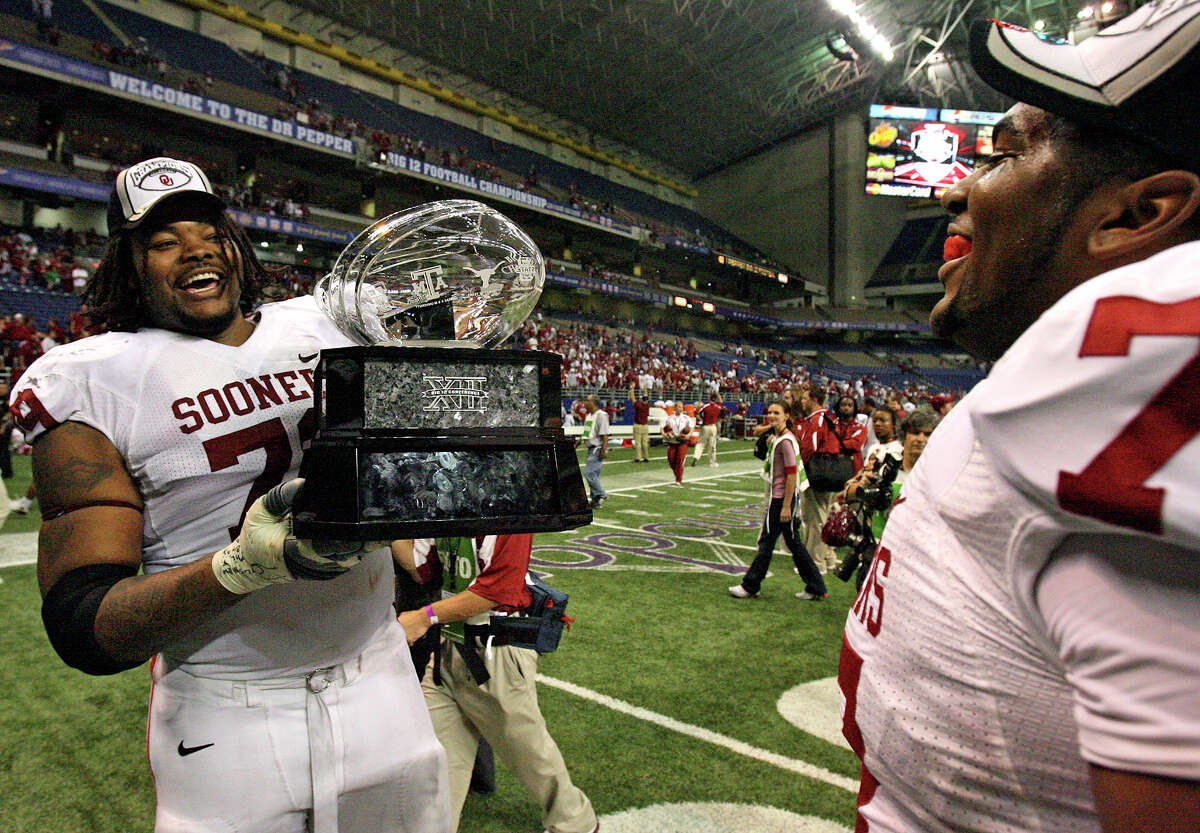 Oklahoma Sooners linemen Phil Loadholt (79) and Sherrone Moore hoist the Big 12 championship trophy as they carry it to fans on the sideline after winning against Missouri, 38-17, at the Alamodome on Dec. 1, 2007.