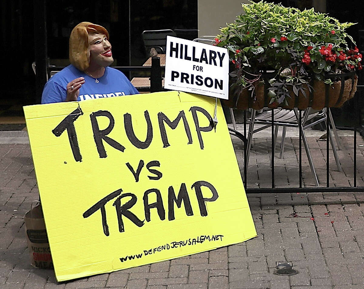 A protester wearing a Hillary Clinton mask and displaying an anti-Hillary poster in downtown Cleveland, Ohio, July 17, 2016 on the eve of the kick-off of the Republican National Convention that runs July 18-21.