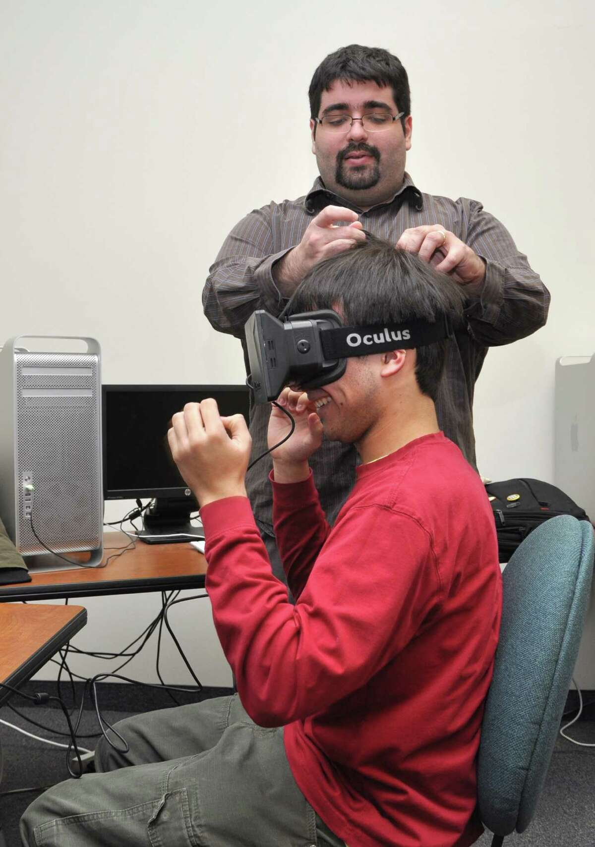 Ibrahim Yucel, a SUNY Polytechnic Institute assistant professor and faculty lead for the school's new interactive media and game design degree program, works with a student using the Oculus Rift virtual-reality headset.