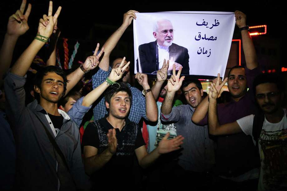 """FILE -- In this July 14, 2015 file photo, young Iranian men cheer and show victory signs while holding a picture of Foreign Minister Mohammad Javad Zarif, reading """"Zarif is Mosaddegh of our time,"""" comparing Zarif to Mohammad Mosaddegh, Iran's legendary prime minister during the 1950s who nationalized the country's oil industry, in Tehran, Iran. A document obtained by The Associated Press Monday, July 18, 2016, says key nuclear restrictions on Iran will ease in a little more than a decade, halving the time Tehran would need to build a bomb if it chose to do so. The document says that 11 to 13 years into the 15-year agreement, Iran can replace the 5,060 inefficient centrifuges it now uses to enrich uranium with up to 3,500 advanced machines. (AP Photo/Ebrahim Noroozi, File) Photo: Ebrahim Noroozi, STR / Copyright 2016 The Associated Press. All rights reserved. This material may not be published, broadcast, rewritten or redistribu"""