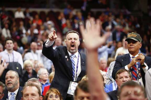 """People chant """"roll-call vote"""" during an attempt by anti-Trump delegates to force a roll-call vote on convention rules on the first day of the Republican National Convention, at the Quicken Loans Arena in Cleveland, July 18, 2016. (Eric Thayer/The New York Times)"""