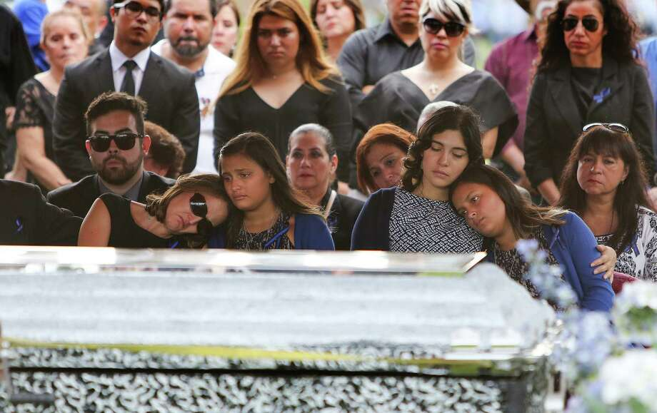 Cecilia Zarate (left) puts her head on the shoulder of her daughter, Miah, (third from right), as her oldest daughter Meghan (second from right) comforts third sister, Mayah, during the graveside service for their husband and father Bellaire police Officer Anthony Zarate Monday, July 18, 2016, in Houston.  Zarate was killed in a high-speed chase through the streets of Bellaire after a suspected shoplifter. Photo: Steve Gonzales, Houston Chronicle / © 2016 Houston Chronicle