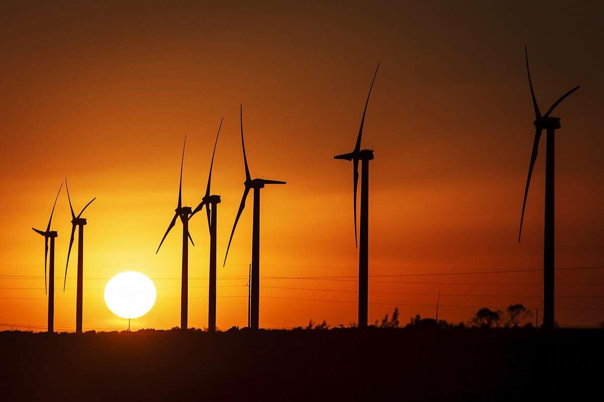 The sun sets behind several 285ft tall 2.5 MW Clipper wind turbines at the BP Sherbino Mesa II Wind Farm, Monday, Feb. 20, 2012, in Fort Stockton.