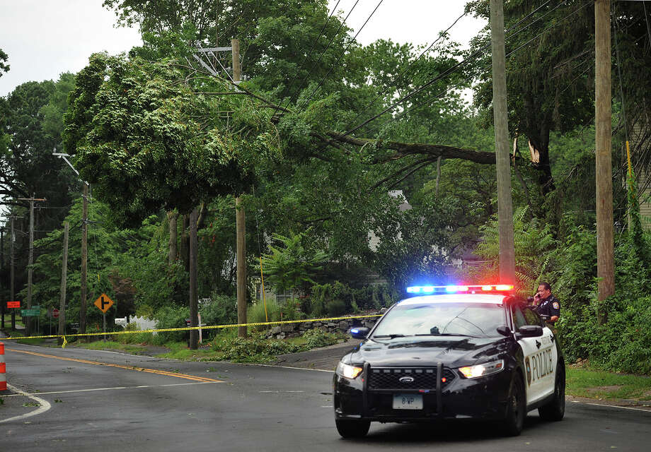 Westport Police close off a section of Main Street below the intersection with North Compo Road after a tree collapsed on overhead powerlines during afternoon storms in Westport, Conn. on Monday, July 18, 2016. Photo: Brian A. Pounds / Hearst Connecticut Media / Connecticut Post