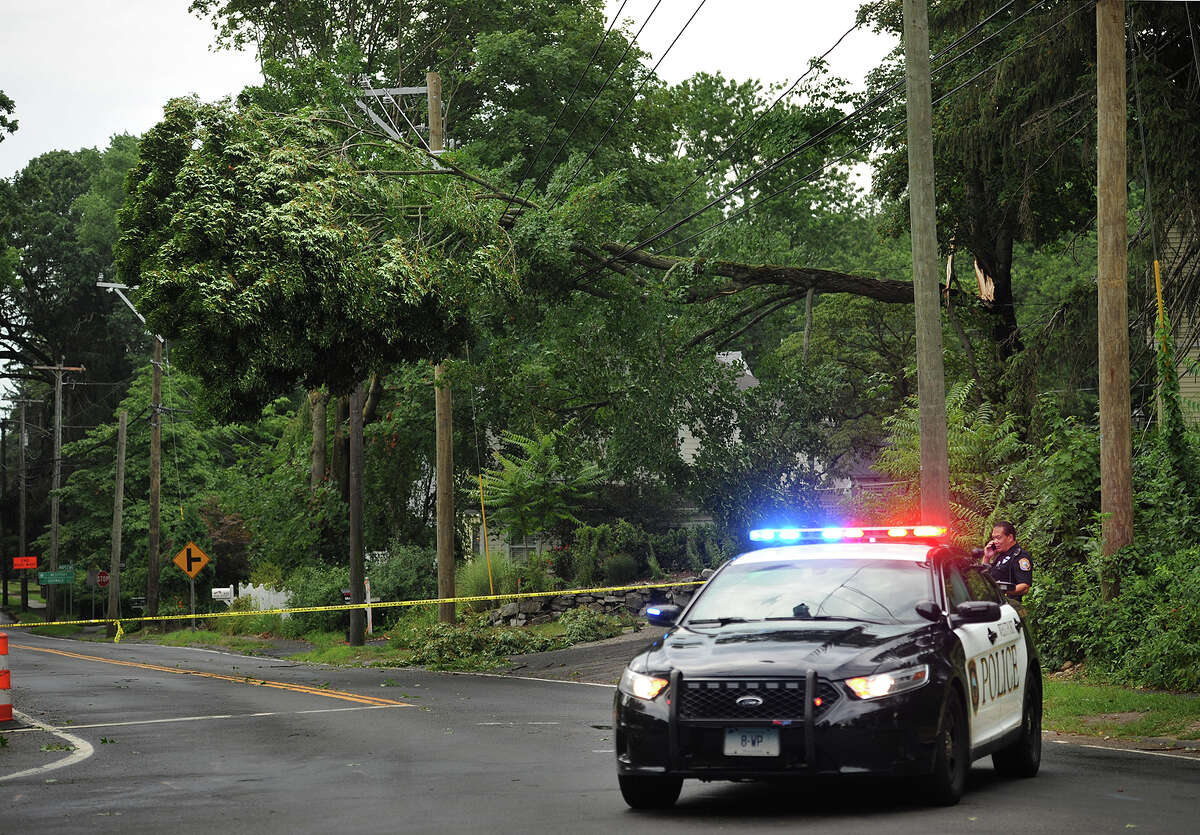 Westport Police close off a section of Main Street below the intersection with North Compo Road after a tree collapsed on overhead powerlines during afternoon storms in Westport, Conn. on Monday, July 18, 2016.