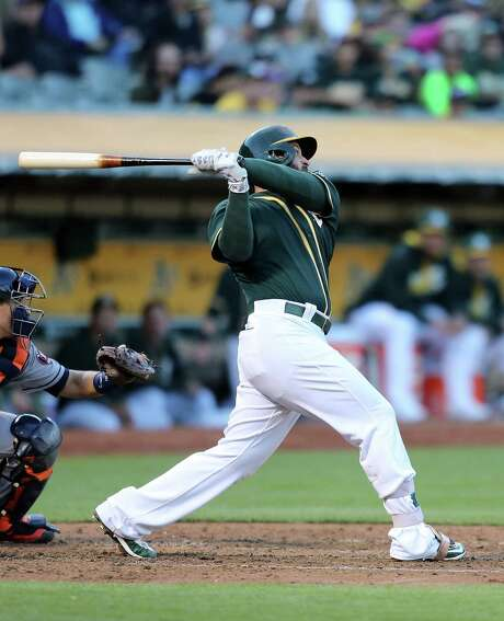 The Athletics' Yonder Alonso doubles off Astros starter Mike Fiers to drive in Marcus Semien in the second inning of Monday night game at Oakland, Calif. For a recap of the game, go to chron.com/astros. Photo: Don Feria, Stringer / 2016 Getty Images