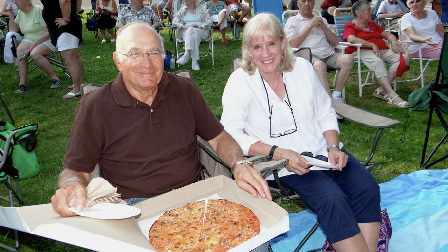 Westporters Harry Gagliardi and Trisha Mears enjoy a Colony Grill pizza and Yesteryear singing oldies at Sherman Green Sunday evening. Photo: Mike Lauterborn / For Hearst Connecticut Media / Fairfield Citizen