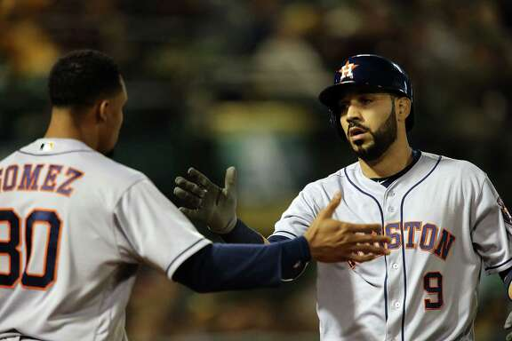 OAKLAND, CA - JULY 18:  Marwin Gonzalez #9 of the Houston Astros  is congratulated by Carlos Gomez #30 after hitting a solo homer in the top of the fifth against the Oakland Athletics at the Oakland Coliseum on July 18, 2016 in Oakland, California.